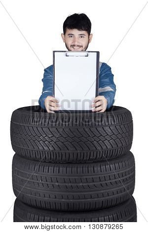 Photo of middle eastern mechanic smiling at the camera while showing empty clipboard above a pile of tires