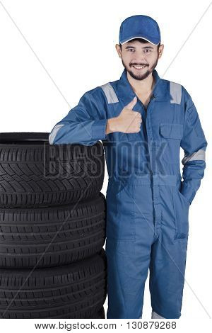 Middle eastern workshop worker standing next to a stack of tires and showing thumb up