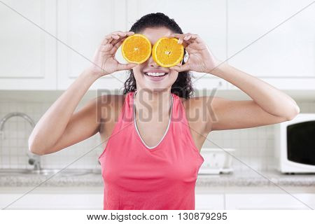 Image of female model holding two piece of fresh orange in front of her eyes shot in the kitchen at home