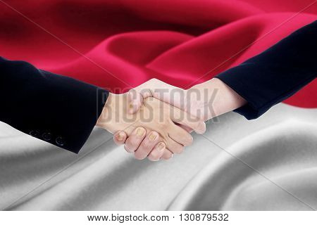 Photo of two worker hands in a formal suit shaking hands with Monaco flag background