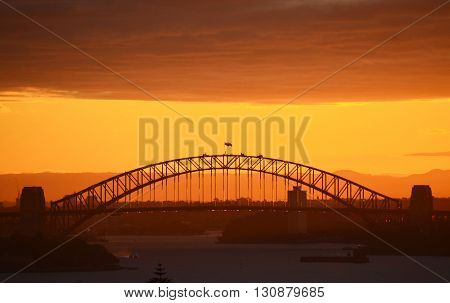 Sydney Harbour Bridge in silhouette at sunset