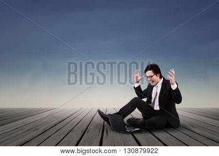 Asian businessman angry and shouting while sitting on the wooden floor