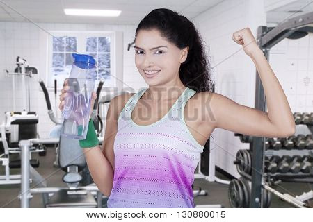 Healthy woman drinking water at the gym while showing her bicep shot in winter time