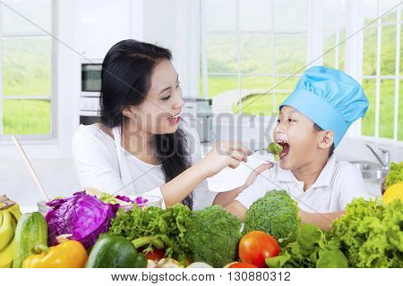 Photo of a young Asian woman feeding her kid with fresh vegetables in the kitchen at home