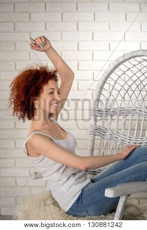 girl sitting on a wicker chair leaning back