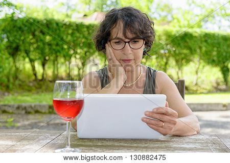 a charming woman with a tablet in her garden