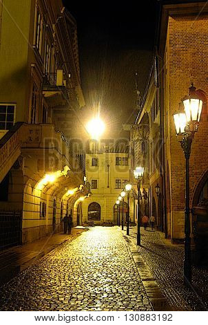 Couples walking along an historic cobblestone street under lamplight in the old city of Prague (digitally altered, accented edges)