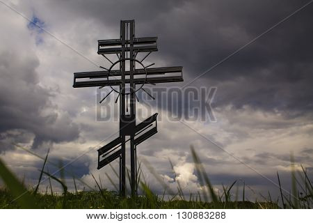 Memorial Christian cross on a background of sky and grass