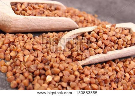 Heap of uncooked brown buckwheat groats with wooden spoon lying on structure of concrete concept for healthy eating and nutrition