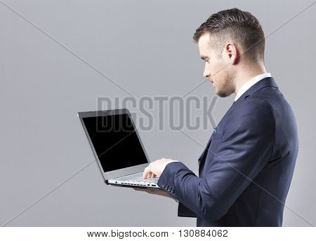 Young businessman using a laptop against grey background