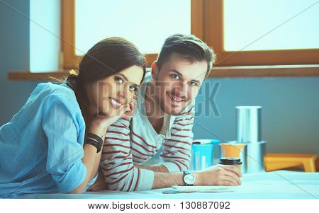 Couple choosing paint colour from swatch for new home lying on wooden floor.