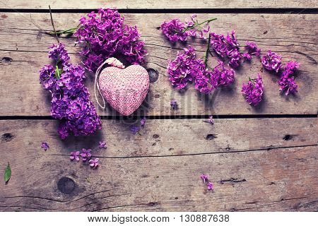 Fresh violet lilac flowers and decorative pink heart on aged wooden planks. Selective focus. Place for text. Flat lay. Top view. Toned image.