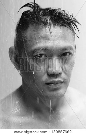 An asian man showering looking at the camera