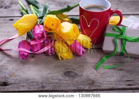 Yellow and pink spring tulips red cup of coffee box with present on vintage wooden background. Selective focus. Place for text.