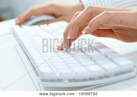 Closeup picture of female hand typing on desktop computer keyboard.