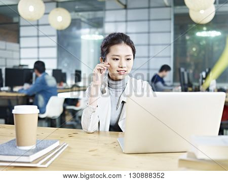young asian business executive sitting at desk in office working using laptop computer.