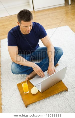 Casual young man using laptop computer at home, sitting at floor, looking at screen. High angle view.