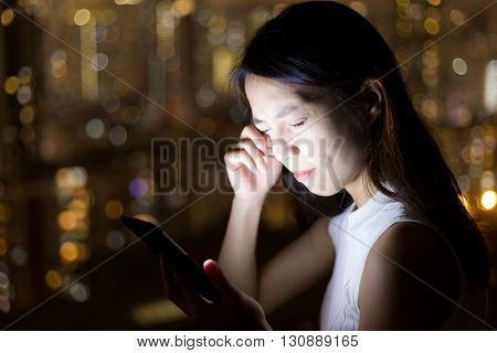 Woman feeling eye pain with mobile phone at night