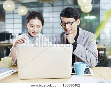 young asian business people sitting at desk working together using laptop computer.