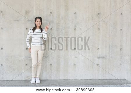 Woman thinking against concrete wall