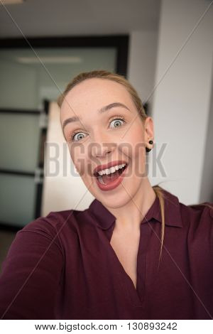 young business woman making selfie and funy surprise face  at office