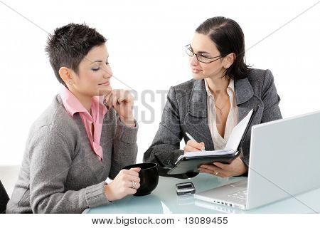 Young businesswomen sitting at office desk, writing in personal organizer, smiling. Isolated on white.