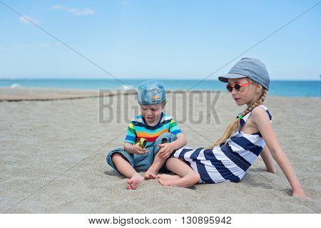 Tho kids in sunglasses sitting on the sandy beach