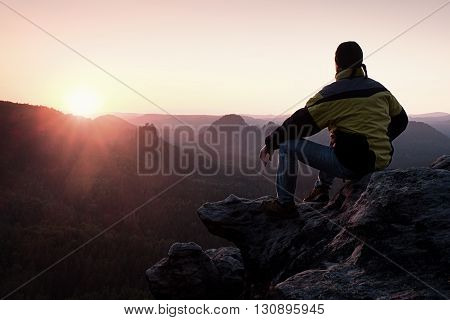 Rear View Of Male Hiker In Yellow Black Jacket Sitting On Rocky Cliff While Enjoying Daybreak Above