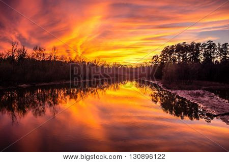 an orange sunset reflection over thw lake