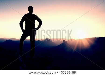 Man Stands On The Peak Of Sandstone Rock In National Park Saxony Switzerland And Watching To Sun. Be