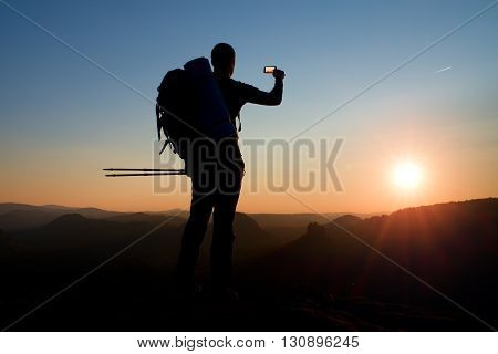 Strong Man Hiker Taking Photo With Smart Phone At Mountain Peak. Daybreak At Horizon