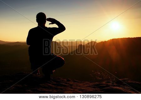 Alone Sportsman In Black. Tall Hiker In Squatting Position Enjoy View At Sunset On Mountain Peak