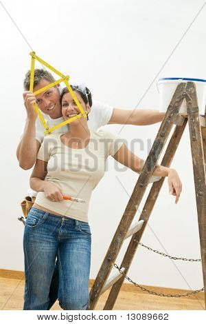 Happy young couple playing with ruler while improving their new home.