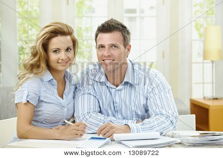 Happy couple sitting at home, planning household financials.