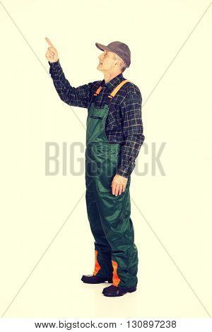 Mature gardener in uniform pointing up