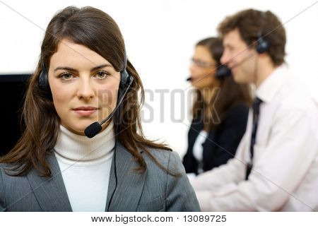 Attractive customer service operator talking on headset, two colleagues sitting in the background.