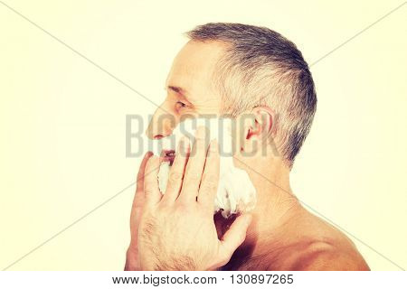 Mature man applying shaving foam