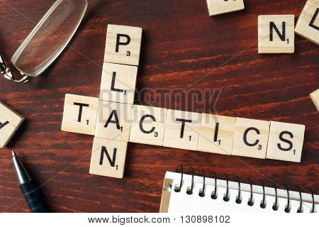 Words Plan Tactics from wooden blocks with letters.