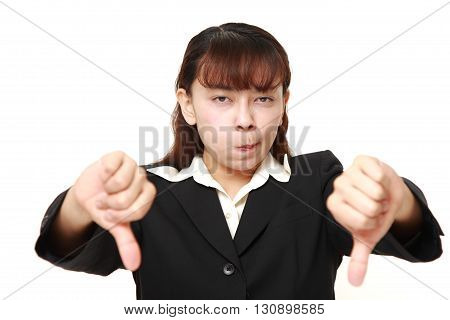 Asian businesswoman with thumbs down gesture on white background