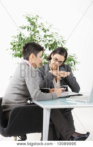 Young businesswomen sitting at office desk, looking at smart phone.