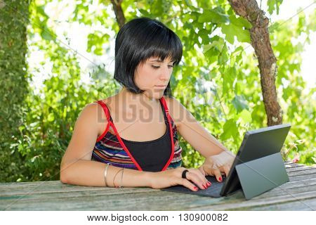 casual woman working with a tablet pc, outdoor