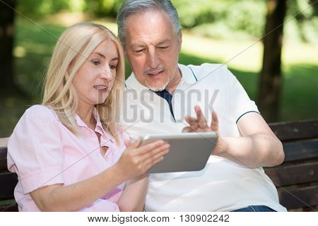 Mature couple using a digital tablet outdoors