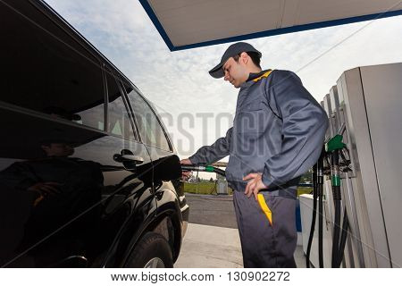 Gas station attendant filling up a car