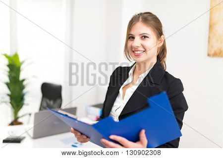 Portrait of a young smiling businesswoman holding a clipboard