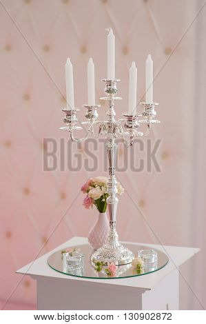 Antique candlestick with wedding bouquet. wedding candlestick with flower decoration before wedding ceremony