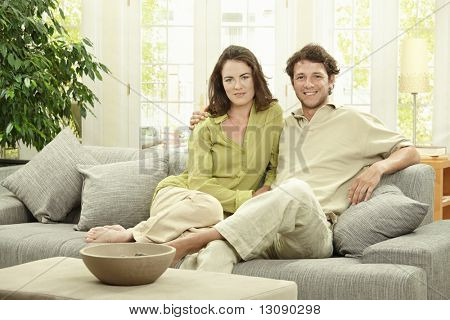Happy young couple sitting together on couch at home, embracing, smiling.