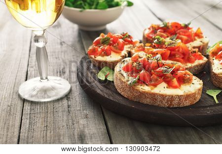 Bruschetta with tomatoes goat cheese and basil on a wooden table with a glass of wine. Tasty appetizer for wine.