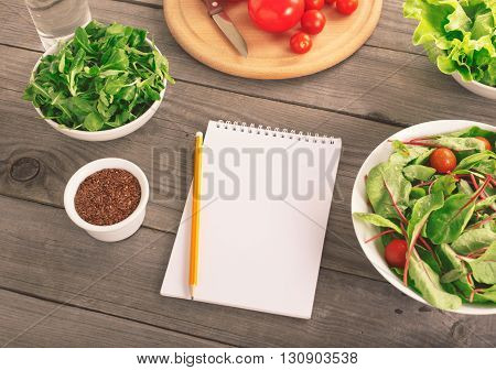 Blank notebook with various salad leaves glass of water tomatos and flax seed. Helpful balanced diet weight loss and diet concept top view