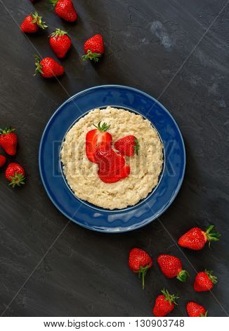 Oatmeal porridge with strawberries on a dark surface. Healthy breakfast image