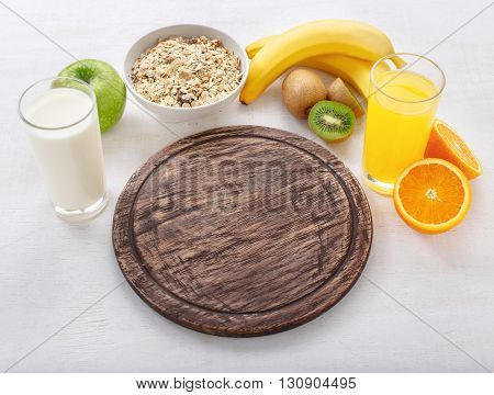 Blank cutting board with ingredients for cooking healthy food on a light surface